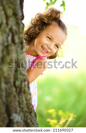 Cute little girl is playing hide and seek, outdoor shoot - stock photo