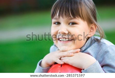 Cute little girl is playing in playground, outdoor shoot - stock photo