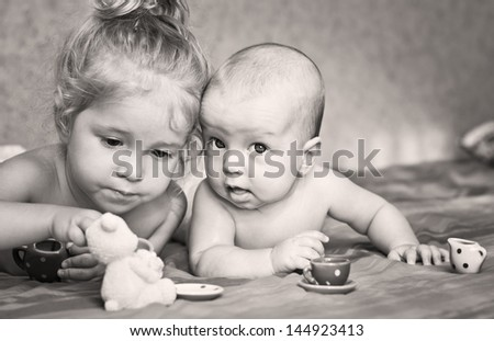 Cute little girl is playing with his younger brother at home lying on the bed with cups - stock photo