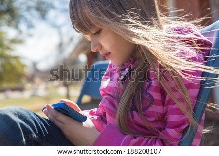 Cute little girl is playing with the smartphone - stock photo