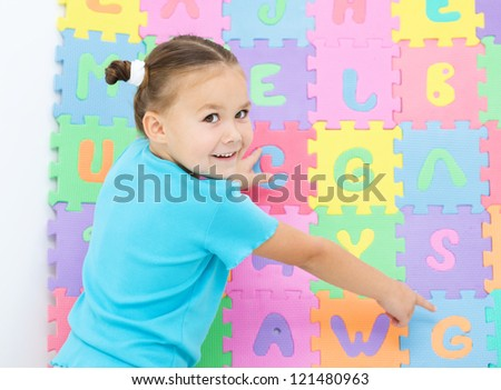 Cute little girl is pointing at letter G on alphabet - stock photo