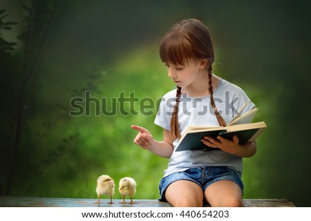 Cute little girl is reading a book to couple yellow chickens outdoors - stock photo