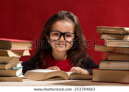 Cute little girl is reading a book while wearing glasses, isolated over red - stock photo