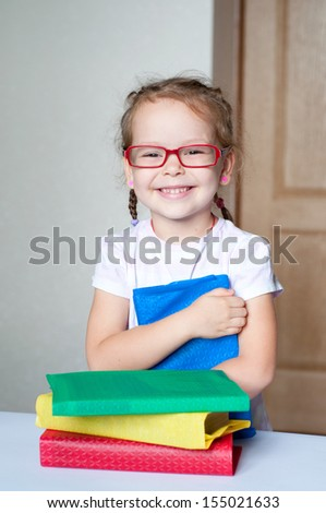 Cute little girl is reading book wearing glasses - stock photo