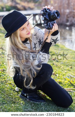 Cute little girl is resting near lake with camera - stock photo