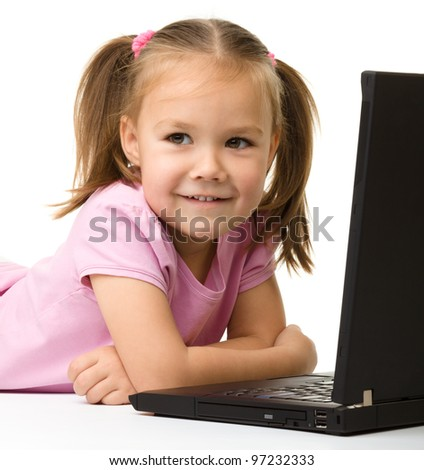 Cute little girl is sitting on floor with her black laptop, isolated over white - stock photo