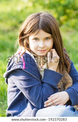 Cute little girl is sitting on the grass and keeps  kitten - stock photo