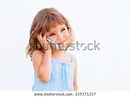 Cute little girl is talking on cell phone - stock photo