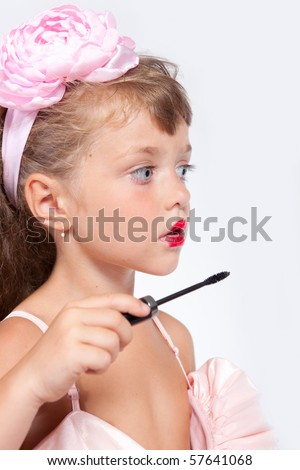 Cute little girl is trying painting her eyelashes - stock photo