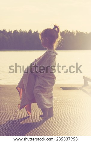 Cute little girl is watching at the sea. Toned - stock photo