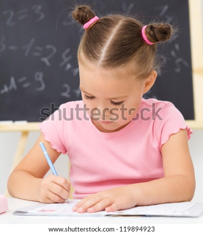 Cute little girl is writing using a pen in preschool - stock photo