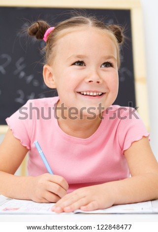 Cute little girl is writing using a pen in school - stock photo