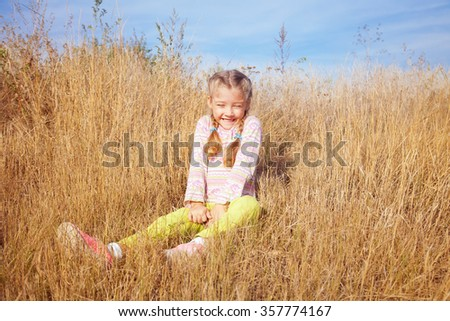 Cute little girl laughing fun outdoors on a bright sunny day - stock photo