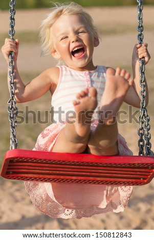 Cute little girl laughs while swinging - stock photo