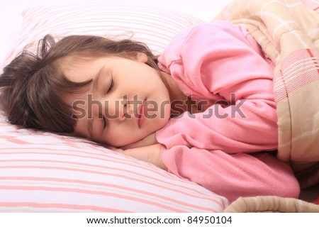 Cute little girl laying in bed sleeping cozy on her pillow and in her blanket - stock photo