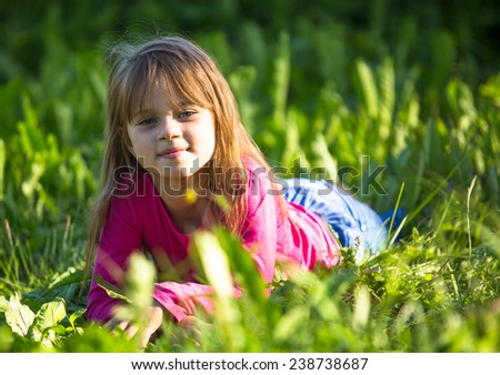 Cute little girl laying in green grass in the park. - stock photo