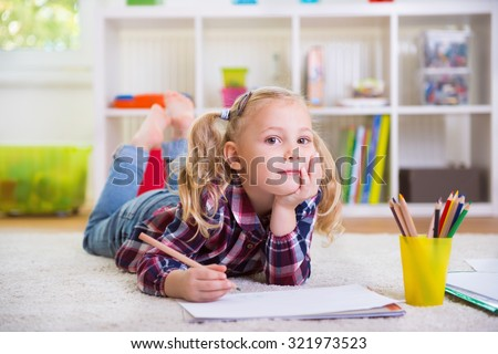 Cute little girl laying on floor at home - stock photo