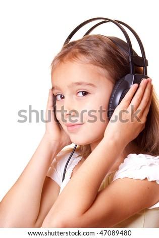 Cute little girl listening music in headphones - stock photo