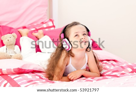 Cute little girl listening music lying on her bed at home - stock photo