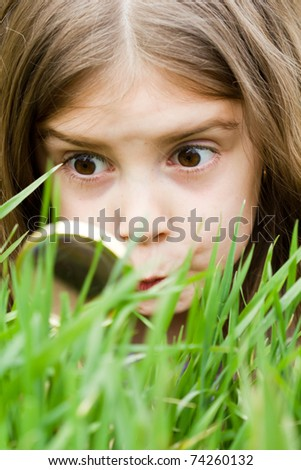 Cute little girl looking at grass through magnifying glass - stock photo