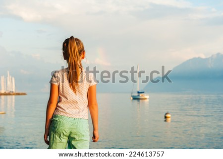 Cute little girl looking at the beautiful lake on sunset - stock photo