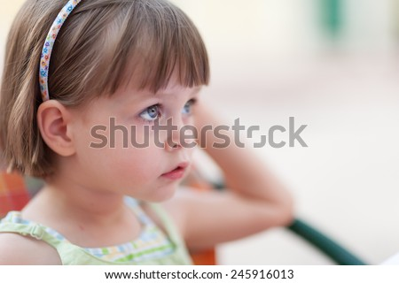 Cute little girl looking for someone or something at coffee table. Closeup portrait with shallow depth of field. - stock photo