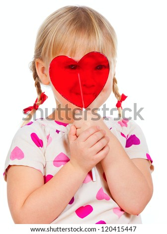 Cute little girl looking through big red heart shaped lolly pop candy - stock photo