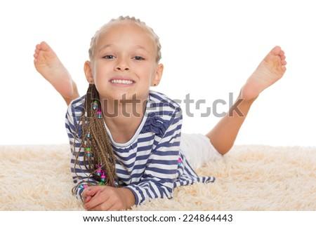 Cute little girl lying on the rug. Girl is six years old.  - stock photo