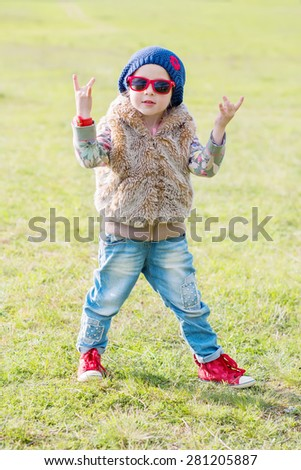 cute little girl making a rock-n-roll sign outdoors - stock photo