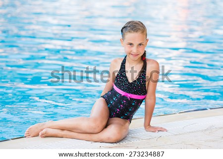 Cute little girl near the swimming pool - stock photo