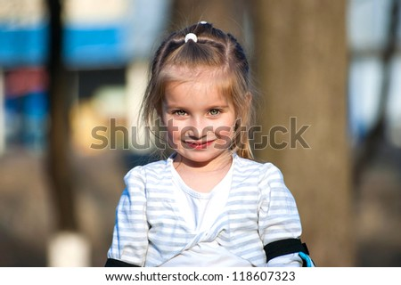 Cute little girl on outdoor playground equipment - stock photo