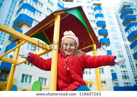 Cute little girl on playground equipment - stock photo