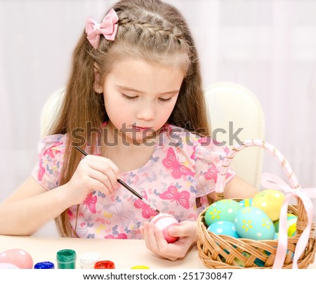 Cute little girl painting colorful easter eggs  - stock photo