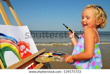 Cute little girl paints on the beach - stock photo