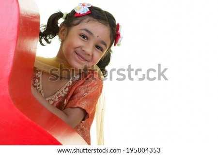 Cute Little Girl Peeking From Behind a Red Curved Wall - stock photo