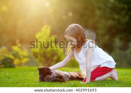Cute little girl petting a giant black cat outdoors - stock photo