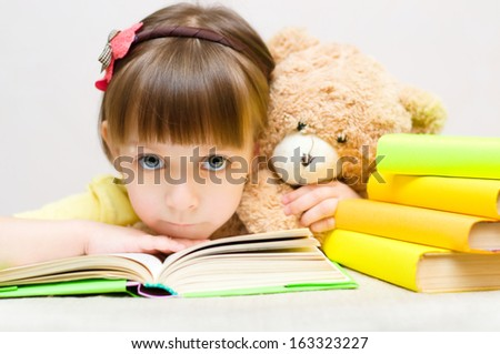 Cute little girl play with book and toy bear while sitting at table - stock photo