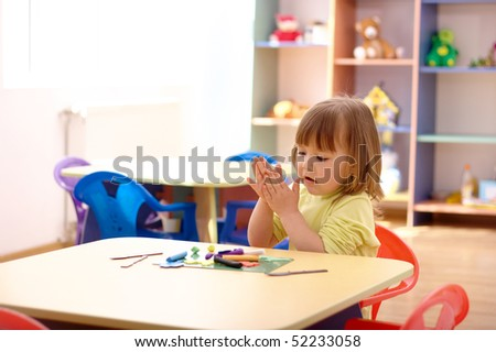 Cute little girl play with plasticine in preschool - stock photo