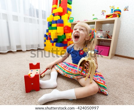 Cute little girl playing and eating banana in daycare - stock photo