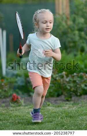 Cute little girl playing badminton on green grass outdoor.  - stock photo