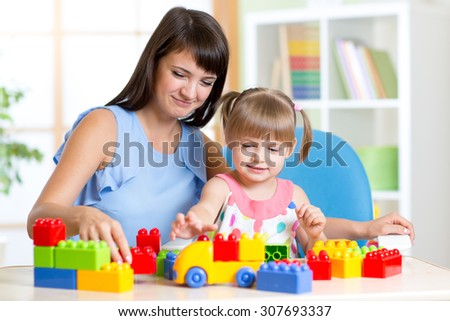 Cute little girl playing block toys with mother at home - stock photo