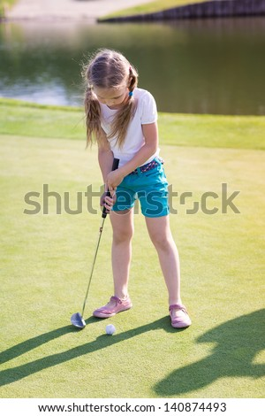 Cute little girl playing golf on a field outdoor - stock photo