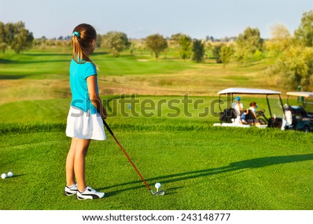 Cute little girl playing golf on a field outdoor. Summertime - stock photo