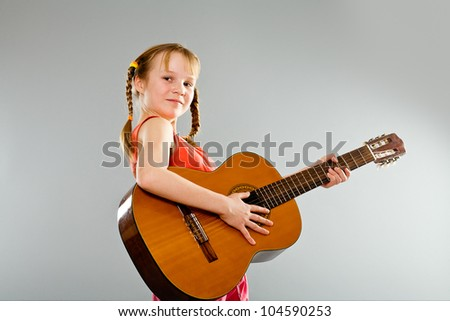 Cute little girl playing guitar - stock photo