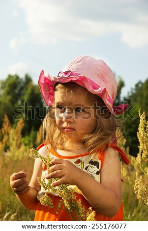 Cute little girl playing in meadow at sunset - stock photo