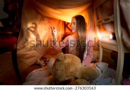 Cute little girl playing in shadow theater in bedroom at night - stock photo