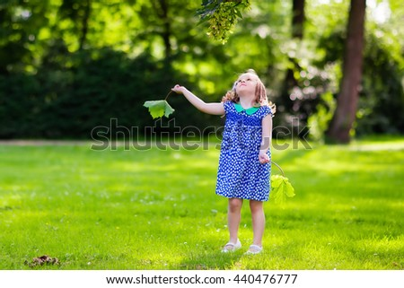 Cute little girl playing in sunny summer park. Child picking maple leaves. Toddler kid running and jumping in a forest. Kids play outdoors. Children run. Preschooler in school yard on warm autumn day. - stock photo