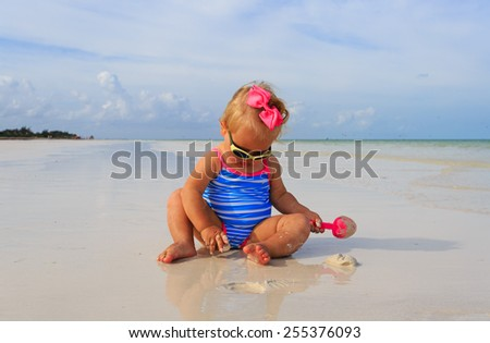 cute little girl playing on summer beach - stock photo