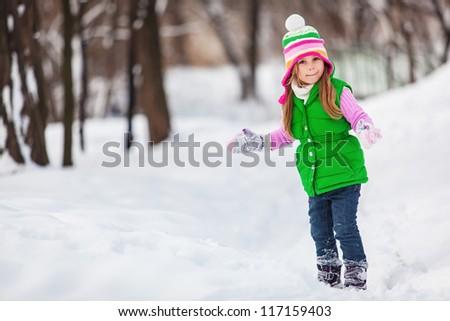 Cute little girl playing snowballs - stock photo