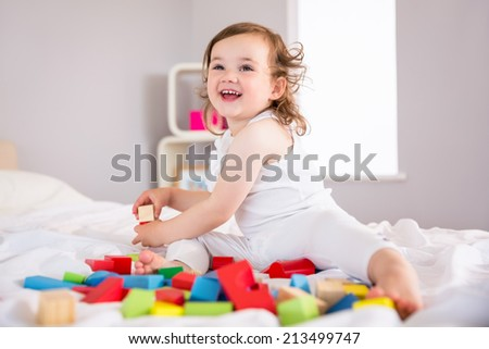 Cute little girl playing with building blocks on bed at home - stock photo
